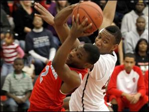 Bowsher's Aundre Kizer grabs a rebound from Rogers' Kurtis Jeffery.