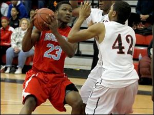 Bowsher's Nate Allen is guarded by Rogers' Fadil Robinson, center, and Kurtis Jeffery.