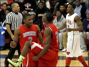 Bowsher's Aundre Kizer, left, and Dajuan King celebrate drawing a foul from Rogers during 2nd half.