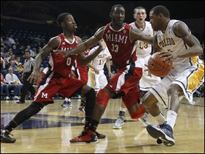 Miami's Geovonie McKnight (0) and Will Felder (33) guard Toledo's Rian Pearson.