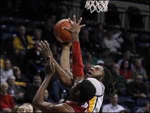 Miami's Jon Harris fouls Toledo's Reese Holliday.