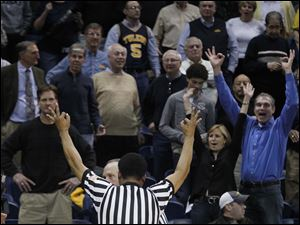 After reviewing the last-second 3-point shot by Toledo's Nathan Boothe, the refs signal the shot was counted, giving UT the win.