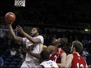 Toledo's Reese Holliday gets past Miami defenders to put a shot up.