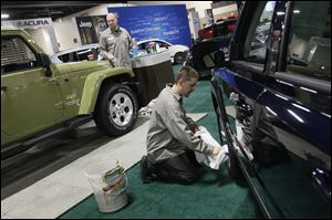 Detailer Joshua Pirrwitz, left, and Yark Automotive Group Detail Manager Karac Isom joke as they polish Jeeps before the start of the Greater Toledo Auto Show today at SeaGate Convention Centre in Toledo. The event runs through Sunday. Tickets are $6 for adults and $4 for those 55 and over.
