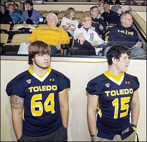 University of Toledo recruits Boston Mathews, 17, of Illinois, left, and Logan Woodside, 18, of Kentucky, listen as head coach Matt Campbell announces his team's recruiting class to fans Wednesday at Savage Arena. Woodside may have the inside track on the backup quarterback spot to Terrance Owens based on his participation in spring ball.