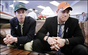 Drew Savage, left, and Jake Nachtrab, seniors at St. John's Jesuit High School, talk about their friend and former classmate, Brian Hoeflinger of Ottawa Hills, after a national signing day event Wednesday.