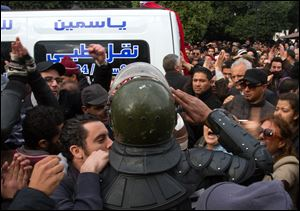 A riot police officer salutes the ambulance carrying the body of Chokri Belaid  after he was shot to death in today Tunis.