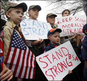 "Clockwise from left,  Boy Scouts Eric Kusterer, Jacob Sorah, James Sorah, Micah Brownlee, and Cub Scout John Sorah hold signs at the ""Save Our Scouts"" Prayer Vigil and Rally on Wednesday at Scouts national headquarters in Irving, Texas."