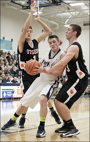 Lake's Connor Bowen (32) tries to get past Otsego's Tommy Rodgers (1) and Ryan Smoyer (23). Bowen scored a game-high 22 points in the win.