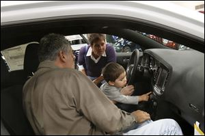 Frank, left, and Lisa Keating, of Florida, examine the interior of the 2013 Dodge Charger with their grandson Kaemon, 19 months, who's sitting on the lap of his father, Derek Eisel of Toledo.