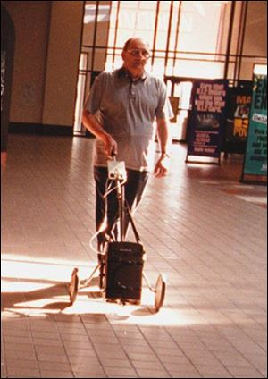 Butch Lemke's fight against beryllium disease includes walks with his oxygen tank attached to an old golf cart.