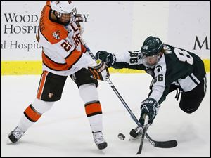 Bowling Green State University center Ryan Carpenter (22) takes a shot against Michigan State's Greg Wolfe (86).