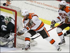 Bowling Green State University center Ryan Carpenter (22) takes a shot against Michigan State goalie Will Yanakeff (37).
