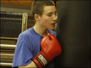 Justen Sykes 17yrs from Oregon, holds the bag while a friend punches.