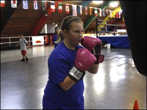 Camry Cook, 11, from Toledo, warms-up while punching the bag. she has been coming to IBC for 2 years.