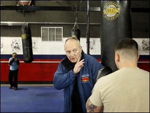 Executive director Harry Cummins, center, works with a boxer on his form.