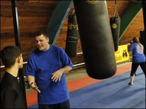 Cody Houghtalling, of East Toledo, center, works with a young boxer on his form.