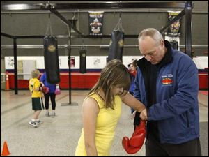 Executive director Harry Cummins, right, helps Ashley Crampton, 13, get her gloves set.