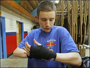 Justen Sykes, 17, wraps his hands. Most of the students just work out, though Sykes has already logged three fights. His record is 2-1.
