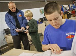 Executive director Harry Cummins, left, helps Lucas Weirich, 13, of Oregon, center, with his math homework while Justen Sykes, 17, right, reviews for his law exam. In addition to helping kids stay in school, Cummins says the program, which he founded 15 years ago, is also offering vocational training for kids who want to become electricians, carpenters or plumbers.