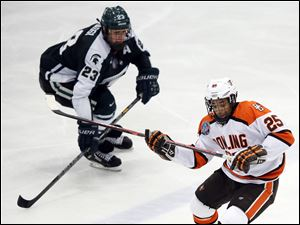 Bowling Green State University left wing Dajon Mingo (25) moves the puck against against Michigan State' s Matt Grassi (23).