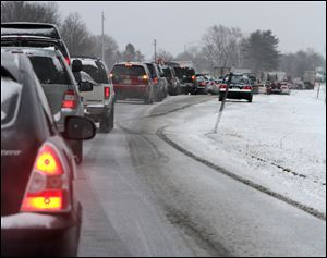 Cars are stuck in traffic as a winter storm arrives in Newington, N.H. Snow began to fall around the Northeast on Friday at the start of what's predicted to be a massive, possibly historic blizzard, and residents scurried to stock up on food and supplies ahead of the storm.