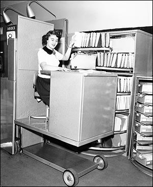 In 1953, a woman remains seated as she files paperwork using a hydraulic lift in Chicago. In the last 60 years, machines have become smarter, smaller, and more efficient.