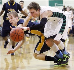 Toledo Christian's Eric Cellier, left, battles with Ottawa Hills'  Blake Pappasfor a loose ball at Ottawa Hills High School.