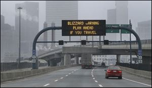 A warning sign flashes for motorists on the expressway into Boston as snow starts to fall.