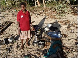 A woman stands next to her belongings she found along a beach at Venga village after tsunami hit Temotu province, Solomon Islands.