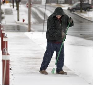 Toledoan Luis Perez sweeps a dusting of snow off a sidewalk near the Hose Sales Direct parking lot at Broadway and Newton streets in Toledo, Ohio. Perez is a janitor at the business.