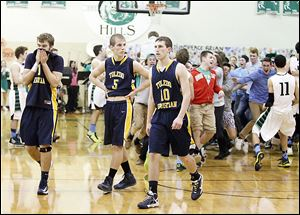 Toledo Christian's Ben Ivan (11), Eric Cellier (5), and Josh Winzeler leave the court after being denied a share of the conference title by Ottawa Hills.