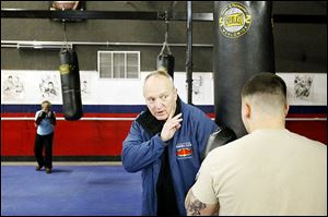 Executive director Harry Cummins works with a boxer on his form during practice at the International Boxing Club in Oregon. Cummins started the club 15 years ago.
