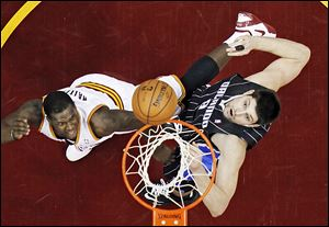 The Cavaliers' Dion Waiters, left, shoots over the Magic's Nikola Vucevic during the second quarter on Friday. It was the third straight win for Cleveland.