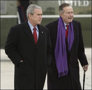 President George W. Bush walks with his father, former President George H.W. Bush, at Andrews Air Force Base, Md.