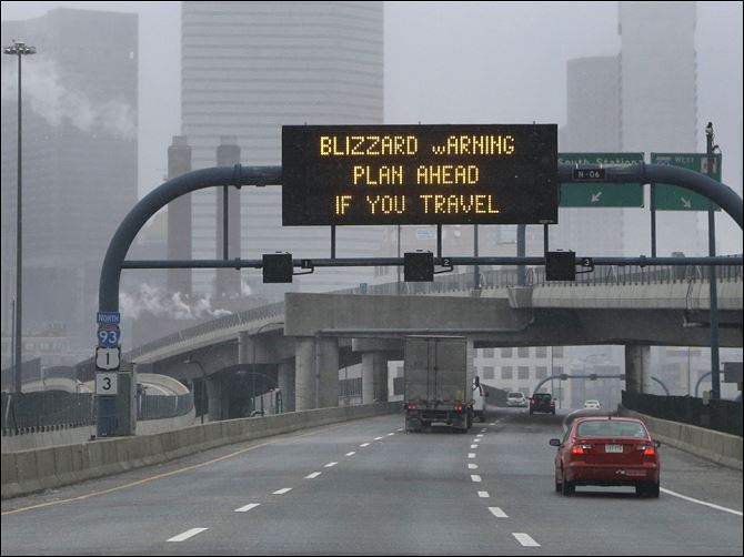A warning sign flashes for motorists A warning sign flashes for motorists on the expressway into Boston as snow starts to fall.