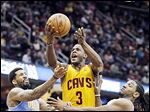Cavaliers guard Dion Waiters (3) shoots between Denver's Wilson Chandler, left, and Kenneth Faried.