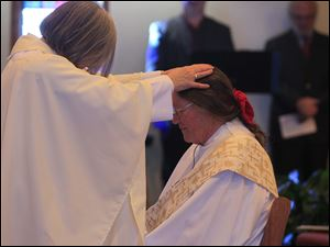 Bishop Joan Houk laying on hands during the ordination of priest Beverly Bingle.