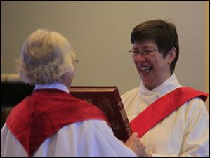 Rev. Elsie McGrath, of St. Louis, left, hands the New Testament to deacon Ann Klonowski.