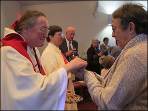 Rev. Beverly Bingle, left, giving communion to Celia Johnson, right, of Bowling Green.