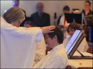 Bishop Joan Houk laying on hands during the ordination of deacon Ann Klonowski.