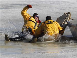 Emergency personnel fall through a thin sheet of ice,