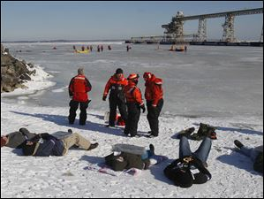 Rescued victims wait on the shoreline of Lake Erie.