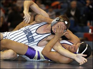 Maumee wreslter Anthony Arroyo, right, gets a hand in the face of Napoleon's Logan Mahlman as he turns him to his back during their 138-pound final match. Arroyo won the match.