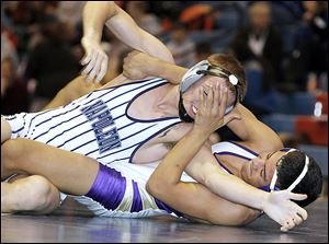 Maumee's Anthony Arroyo, right, gets a hand in the face of Napoleon's Logan Mahlman as he turns him to his back on his way to victory in the 138-pound final.