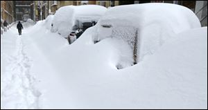 A man walks past snow covered cars in the Chinatown neighborhood of Boston.