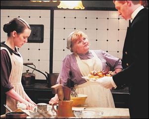 Cook Mrs. Patmore (Lesley Nicol), center, talks to footman Alfred Nugent (Matt Milne) as assistant cook Daisy Mason (Sophie McShera) stands listening in a scene from PBS' Downton Abbey.