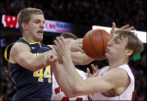 Michigan's Max Bielfeldt, left, and Wisconsin's Sam Dekker vie for a rebound during the first half of an NCAA college basketball game.