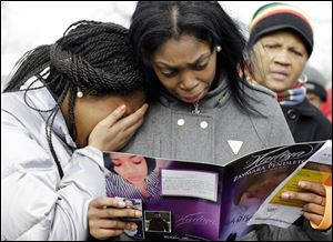 Danyia Bell, left 16, and Artureana Terrell , 16, react as they read a program for the funeral of Hadiya Pendleton outside the Greater Harvest Missionary Baptist Church after the funeral service of Hadiya Pendleton today in Chicago.