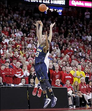 Wisconsin's Ben Brust shoots a long 3-pointer over Michigan's Caris LeVert in the final second of regulation to tie the game.